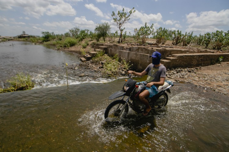 Moto passando com pessoas tomando banho. Passagem molhada no Castanhão
