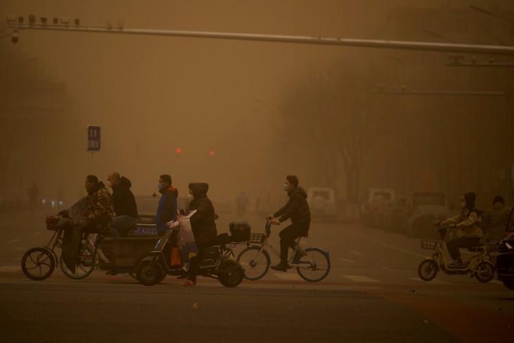 Pessoas atravessam uma rua durante tempestade de areia em Pequim em 15 de março de 2021 (Foto: Noel Celis / AFP)