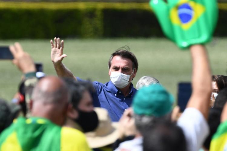 Brasília, 21 de março de 2021: O presidente brasileiro Jair Bolsonaro acena para apoiadores que se reuniram do lado de fora do gramado do Palácio da Alvorada para comemorar seu aniversário, em Brasília, em 21 de março de 2021. (Foto EVARISTO SA / AFP) (Foto: EVARISTO SA/AFP)