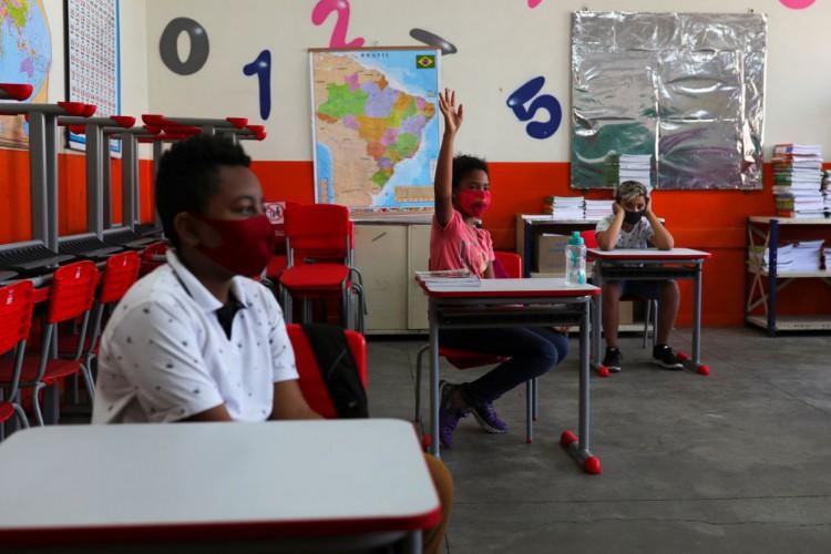 Criança levanta a mão ao lado de outros alunos em sala de aula da escola Thomaz Rodrigues Alckmin, no primeiro dia de retorno das escolas do estado de São Paulo para atividades extracurriculares em meio ao surto de coronavírus (COVID-19) em São Paulo, Brasil Outubro 7, 2020. REUTERS / Amanda Perobelli (Foto: REUTERS / Amanda Perobelli)