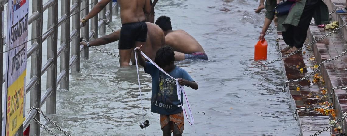 Menino carrega um cordão com ímãs para pescar moedas e outras ofertas valiosas de metal jogadas por devotos hindus no rio Ganges      (Foto: Prakash SINGH / AFP)