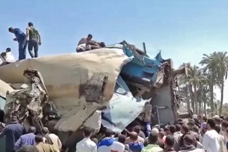 Pessoas reunidas em torno dos destroços de dois trens que colidiram no distrito de Tahta, na província de Sohag no Egito (Foto: STRINGER / EGYPTIAN STATE TV / AFP)