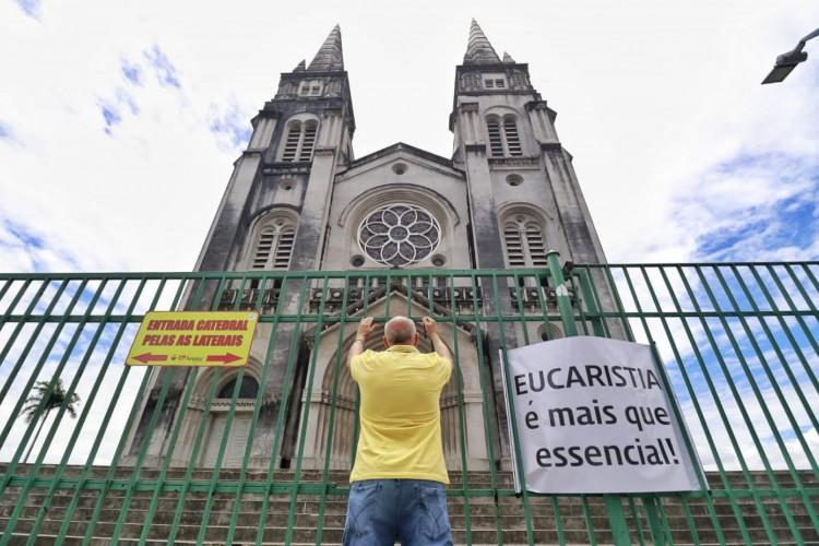 Fiél se ajoelha diante da Catedral de Fortaleza (Foto: Aurélio Alves)