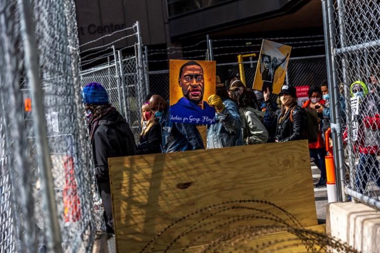 Manifestantes seguram cartazes em homenagem a George Floyd e outras vítimas de racismo durante um protesto em frente ao Centro Governamental do Condado de Hennepin em 28 de março de 2021 em Minneapolis (Foto: Kerem Yucel / AFP)