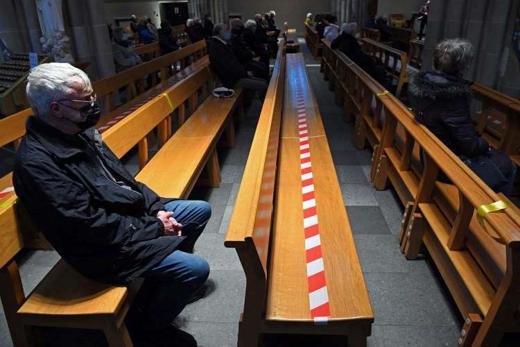 Um devoto usando máscara durante uma missa socialmente distanciada na Catedral de Santo André, em Glasgow  (Foto: AFP)