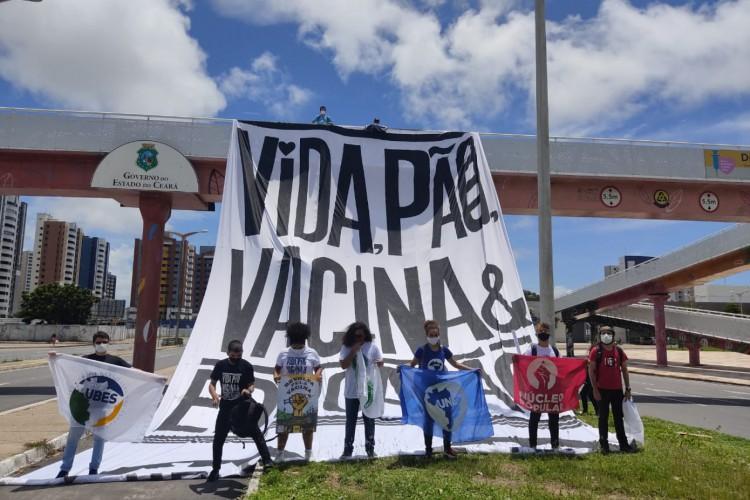 """Cartaz estendido na avenida Washington Soares com os dizeres: """"vida, pão, vacina & educação"""". (Foto: Italo Cosme/O Povo)"""