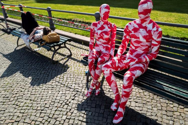 """Manequins enrolados em fita isolante ficam em frente ao famoso Portão de Brandemburgo em Berlim em 31 de março de 2021, como parte do Corona Memorial do artista alemão Dennis Josef Meseg chamado """"It is like it is"""". A mostra em movimento será montada perto de vários pontos de referência da capital alemã nos próximos dias."""