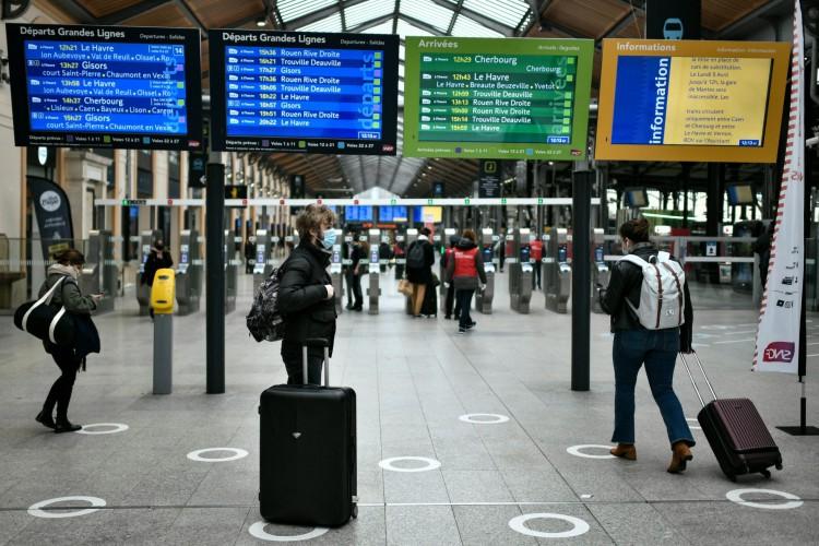 Alguns poucos passageiros esperam, com suas bagagens, na estação de Saint-Lazare em Paris  (Foto: STEPHANE DE SAKUTIN / AFP)