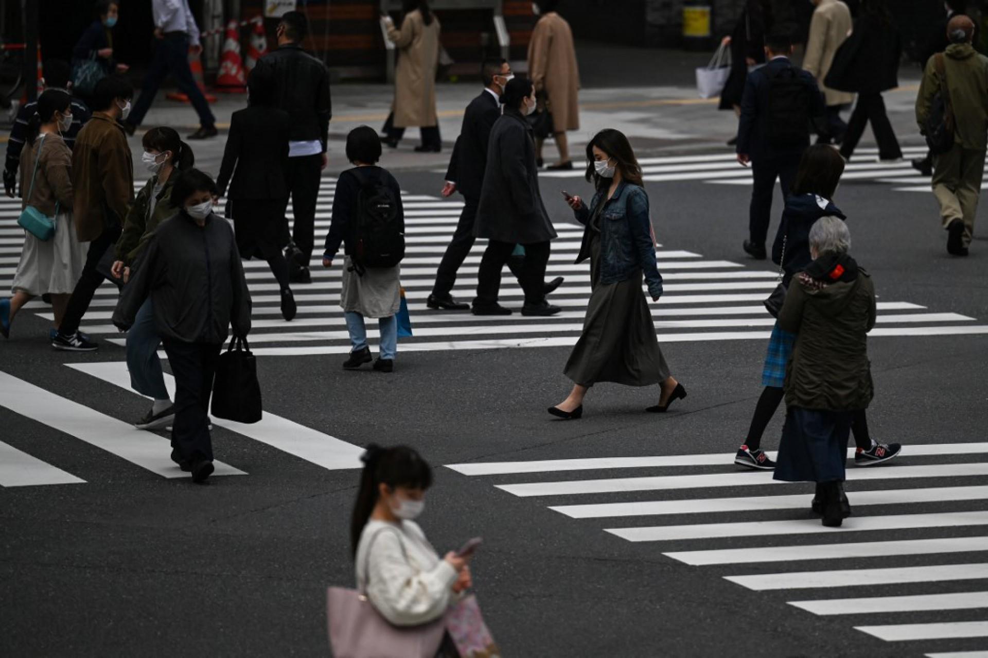 (Foto: Charly TRIBALLEAU / AFP)Olimpíada de Tóquio 2020. Pessoas atravessam uma rua em Tóquio em 9 de abril de 2021.