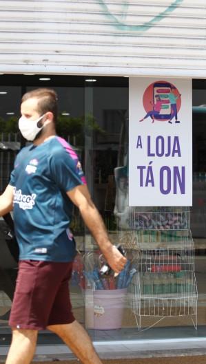 """A loja tá on"" com portão semiaberto, na Paranbaga, durante o lockdown (Foto: FABIO LIMA)"