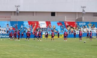 Jogadores batem bola no gramado em treino do Fortaleza; ao fundo, mural de conquistas no Centro de Excelência Alcides Santos, no Pici