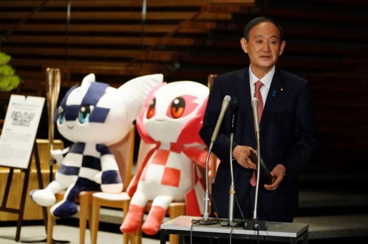 O primeiro-ministro japonês Yoshihide Suga, ao lado dos mascotes dos Jogos Olímpicos e Paraolímpicos de Tóquio 2020(Foto: Eugene Hoshiko / POOL / AFP)