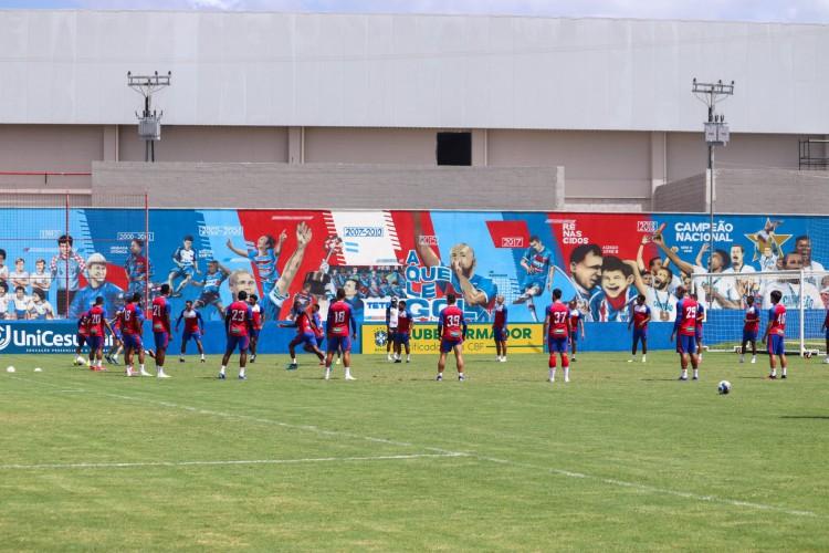 Jogadores batem bola no gramado em treino do Fortaleza; ao fundo, mural de conquistas no Centro de Excelência Alcides Santos, no Pici (Foto: Leonardo Moreira / Fortaleza EC)