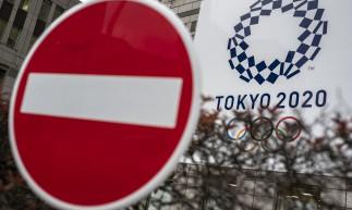Uma placa é vista antes de um banner dos Jogos Olímpicos de Tóquio 2020 exibido na parede do prédio do Governo Metropolitano de Tóquio em Tóquio em 13 de abril de 2021.