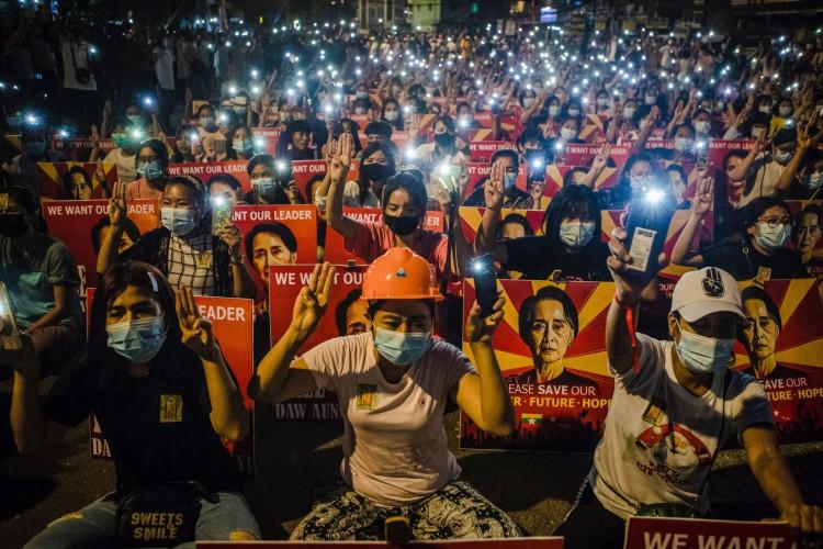 Manifestantes seguram a saudação de três dedos e cartazes com a imagem da líder civil detido Aung San Suu Kyi enquanto usavam suas tochas móveis durante uma manifestação contra o golpe militar em Yangon (Foto: STR / AFP)