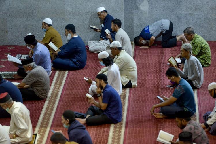 Os muçulmanos leem o Alcorão depois de orar durante o mês sagrado do Ramadã na mesquita Al Makmur em Banda Aceh em 13 de abril de 2021 (Foto: CHAIDEER MAHYUDDIN / AFP)