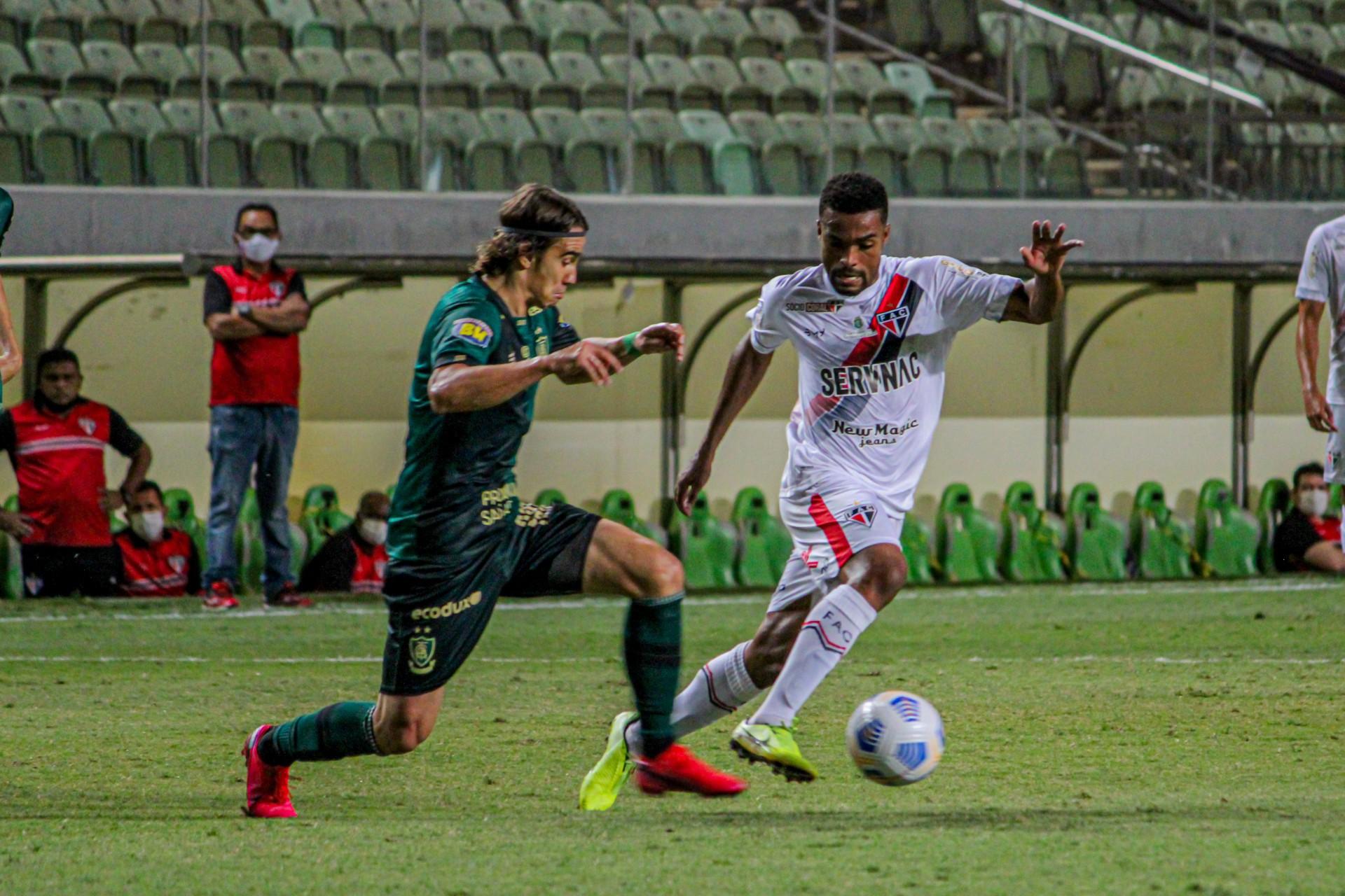 Meia Reinaldo e volante Zé Ricardo disputam bola no jogo América-MG x Ferroviário, na Arena Independência, pela Copa do Brasil