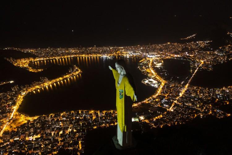 Vista aérea da estátua do Cristo Redentor iluminada com as cores da bandeira brasileira para marcar de para comemorar contagem regressiva para Jogos Olímpicos de Tóquio 2020, no Rio de Janeiro      (Foto: Mauro Pimentel / AFP)