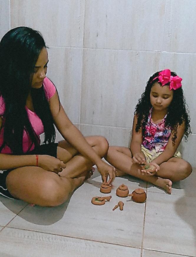 Turma de Alessya Felinto construiu brinquedos que fizeram parte da infância dos pais. Na foto, aluna e mãe trabalham com brinquedos de barro(Foto: Arquivo pessoal/Allessya Felinto)