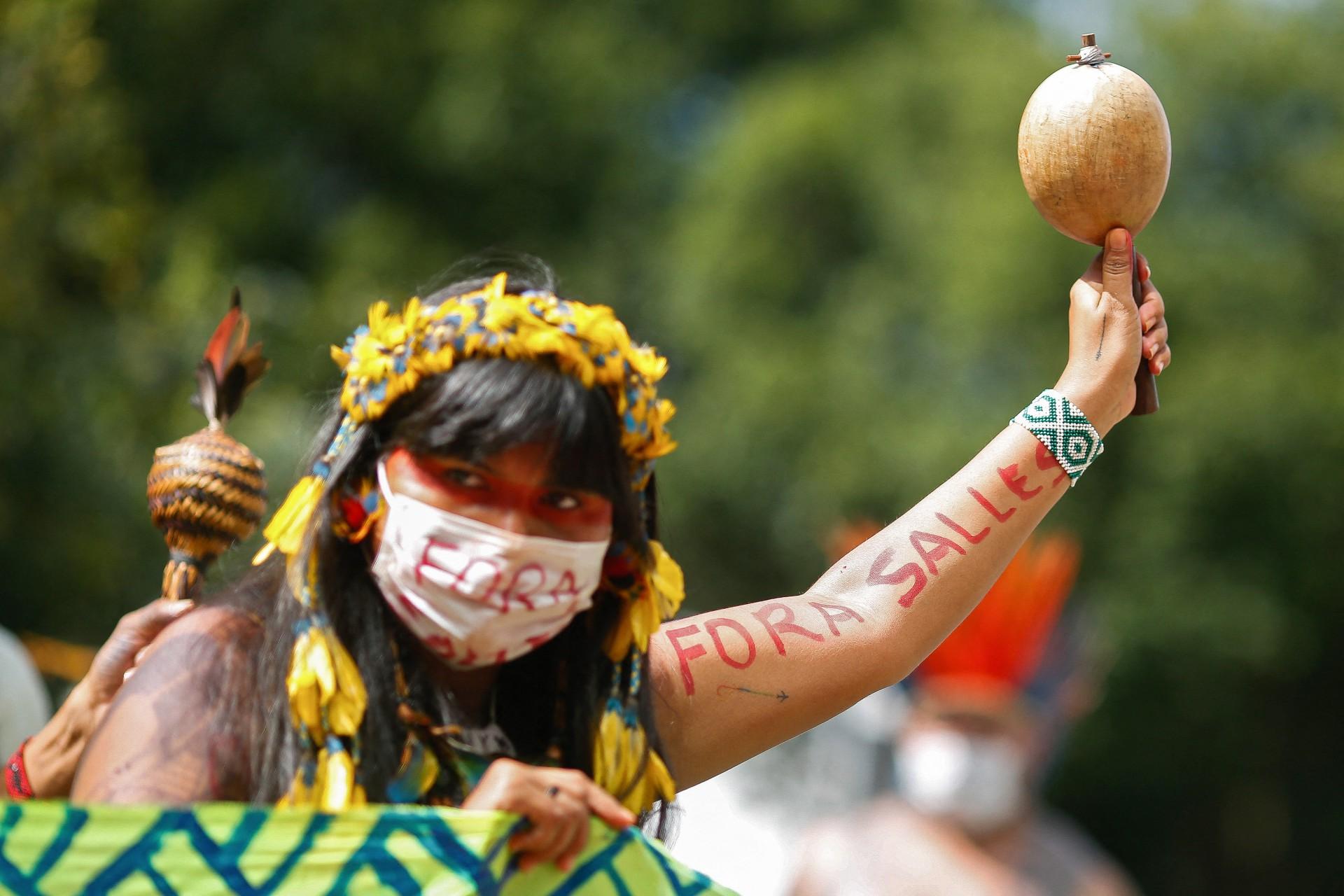 Uma mulher indígena com o braço e uma máscara protetora lendo - Fora Salles, referindo-se ao ministro do Meio Ambiente, Ricardo Salles, participa de um protesto contra a política de mineração do presidente Jair Bolsonaro em relação às terras indígenas, em frente ao prédio do Ministério do Meio Ambiente em Brasília, no dia 20 de abril, 2021, em meio à pandemia de COVID-19. (Foto Sergio Lima / AFP)(Foto: SERGIO LIMA / AFP)