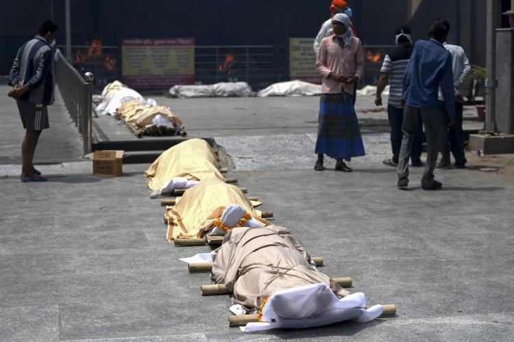 Pessoas estão perto de corpos de vítimas de coronavírus Covid-19 alinhados antes da cremação em um local de cremação em Nova Delhi em 28 de abril de 2021 (Foto: Money SHARMA / AFP)