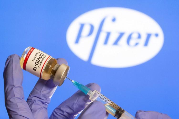 Mulher segura frasco rotulado como de vacina contra Covid-19 em frente a logo da Pfizer em foto de ilustração.30/10/2020 REUTERS/Dado Ruvic (Foto: REUTERS/Dado Ruvic/Direitos reservados)