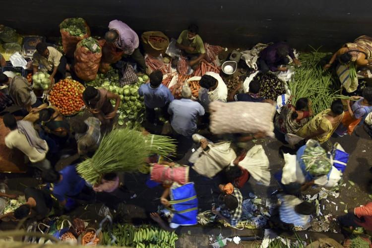 Pessoas usando máscaras como medida preventiva contra a propagação do coronavírus Covid-19 se aglomeram em um mercado atacadista de vegetais durante a madrugada de Mumbai em 1º de abril de 2021 (Foto: Sujit Jaiswal / AFP)