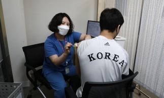 O membro da equipe olímpica de judô da Coréia do Sul, An Ba-ul, recebe a primeira dose da vacina contra o coronavírus Pfizer-BioNTech Covid-19 durante um programa de vacinação para a equipe dos Jogos Olímpicos e Paraolímpicos de Tóquio 2020