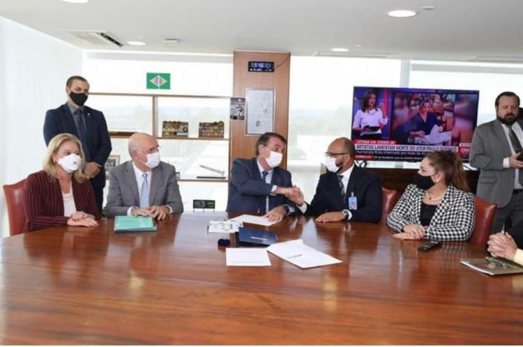 Roque cumprimenta Bolsonaro; ao lado, à mesa, o ministro da Educação Milton Ribeiro