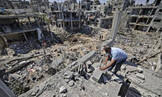Palestinos avaliam os danos causados por ataques aéreos israelenses, em Beit Hanun, no norte da Faixa de Gaza, em 14 de maio de 2021.