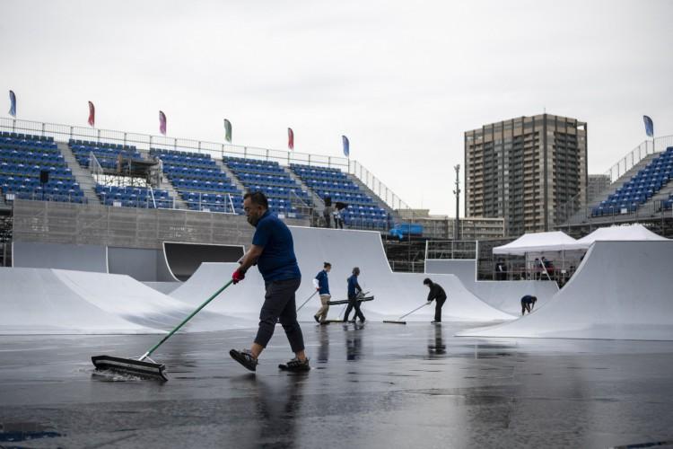 Os membros da equipe varrem a água da chuva do local da pista de estilo livre BMX durante um evento-teste para os Jogos Olímpicos de Tóquio 2020 no Ariake Urban Sports Park em Tóquio em 17 de maio de 2021 (Foto: CHARLY TRIBALLEAU / AFP)