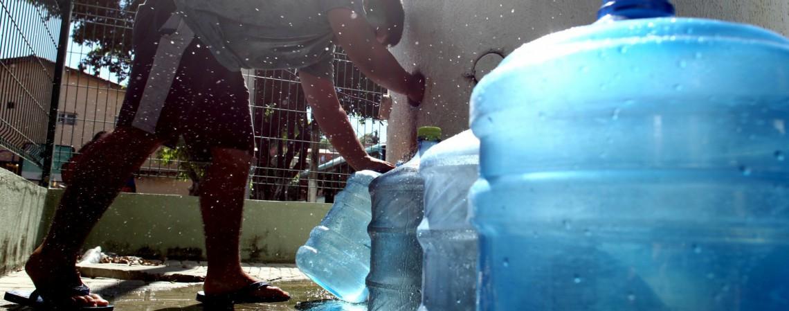 População pega água em chafariz público no Morro Santa Teresinha, em 27 de maio (Foto: FABIO LIMA)
