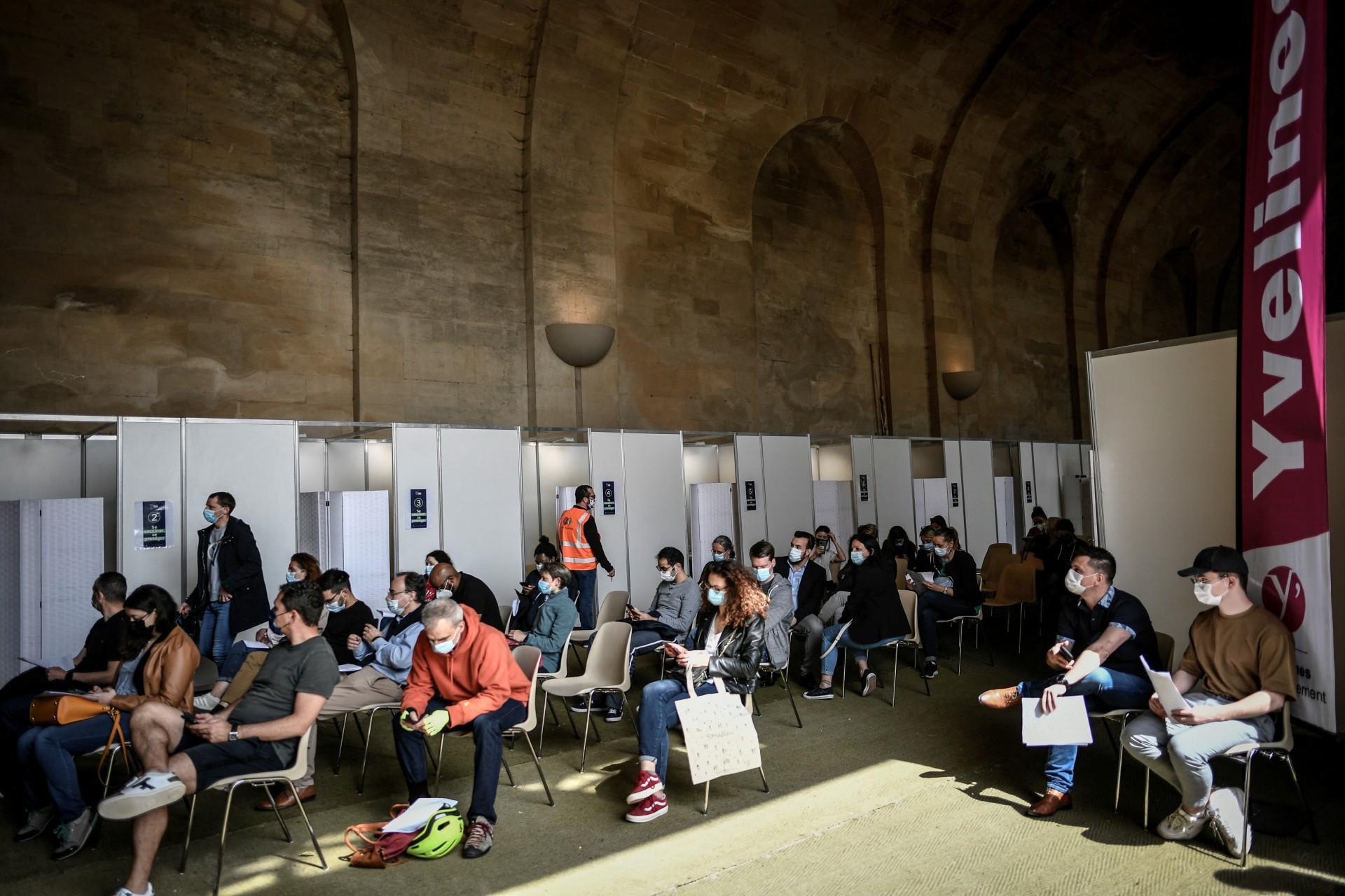 França: As pessoas esperam antes de serem vacinadas contra a Covid-19 no centro de vacinação temporário da Covid-19 na 'Orangerie' do Palácio de Versalhes em Versalhes, em 29 de maio de 2021