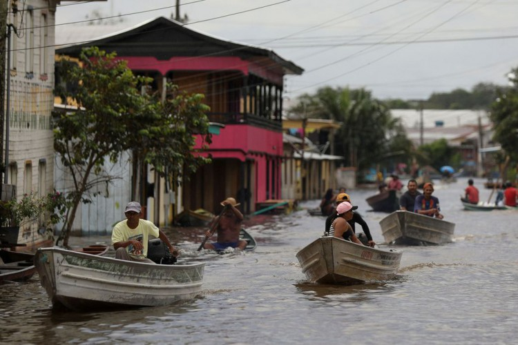 People pass on their boats through a street flooded by the rising Solimoes river, one of the two main branches of the Amazon River, in Anama, Amazonas state, Brazil May 13, 2021. Picture taken May 13, 2021. REUTERS/Bruno Kelly (Foto: REUTERS/Bruno Kelly/Direitos reservados)
