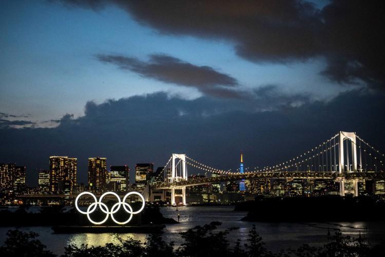 Uma visão geral mostra os anéis olímpicos iluminados ao anoitecer na orla de Odaiba, em Tóquio (Foto: CHARLY TRIBALLEAU / AFP)