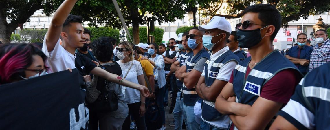 Policiais tunisianos bloqueiam uma estrada enquanto manifestantes protestam contra a violência policial na avenida Habib Bourguiba, na capital Túnis, na Tunísia (Foto: FETHI BELAID / AFP)
