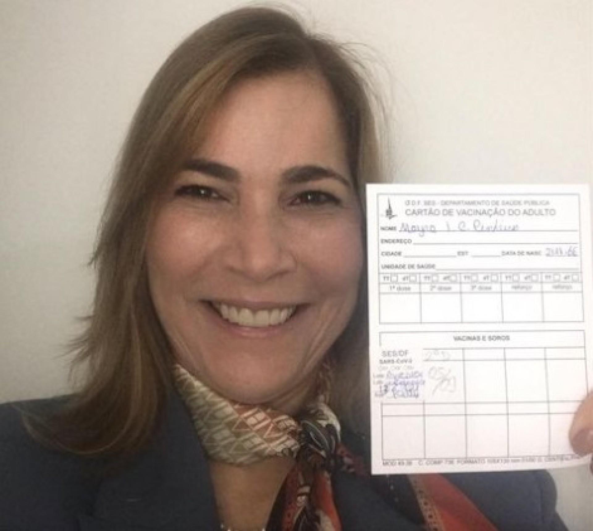 A médica Mayra Pinheiro mostra cartão de vacina contra a covid