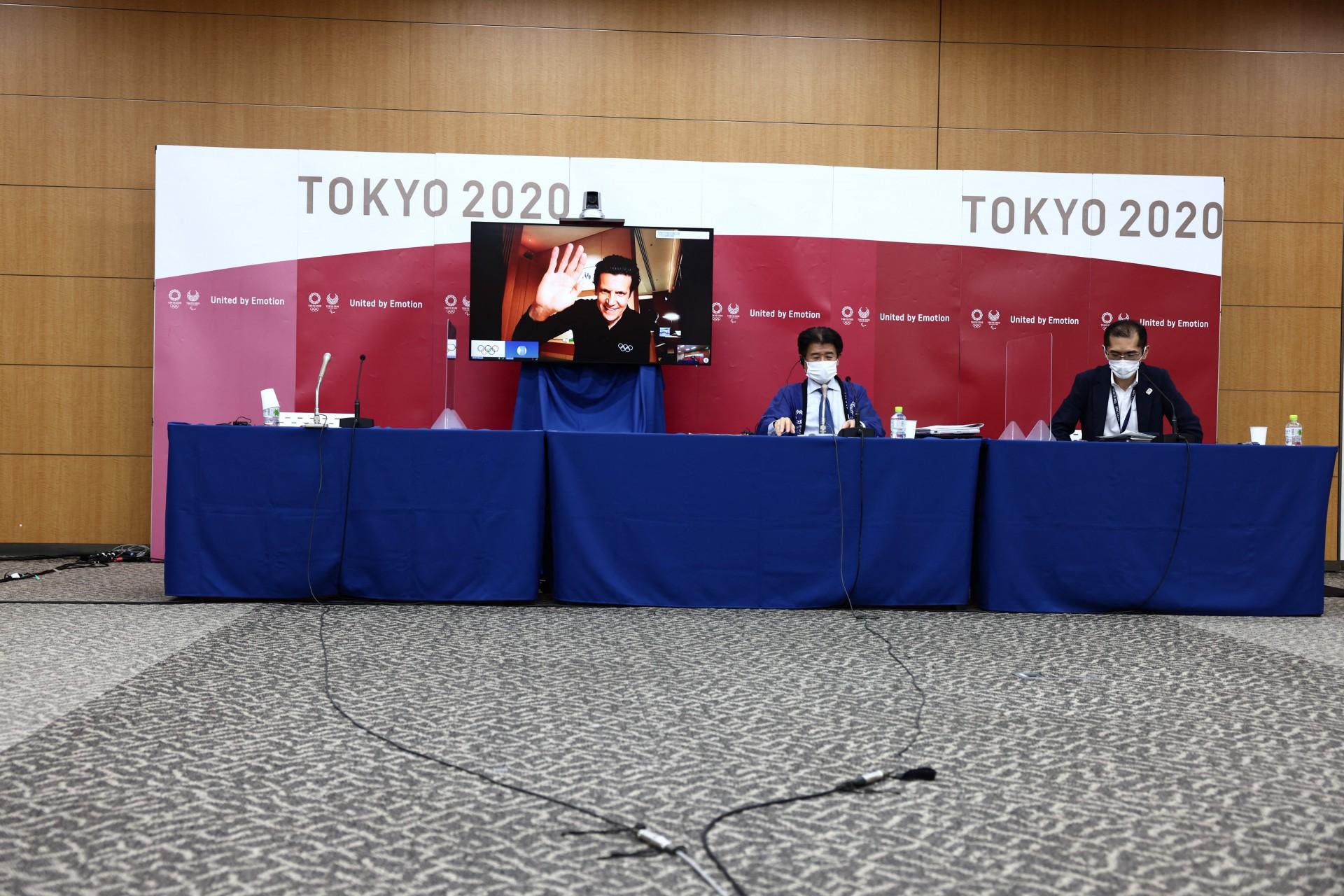 O Diretor Executivo dos Jogos Olímpicos do COI, Christophe Dubi, (na tela) acena enquanto o Chefe da Operação Principal de Tóquio 2020, Hidemasa Nakamura,  e o porta-voz do Tóquio 2020, Masa Takaya, são vistos na conclusão de uma coletiva de imprensa online
