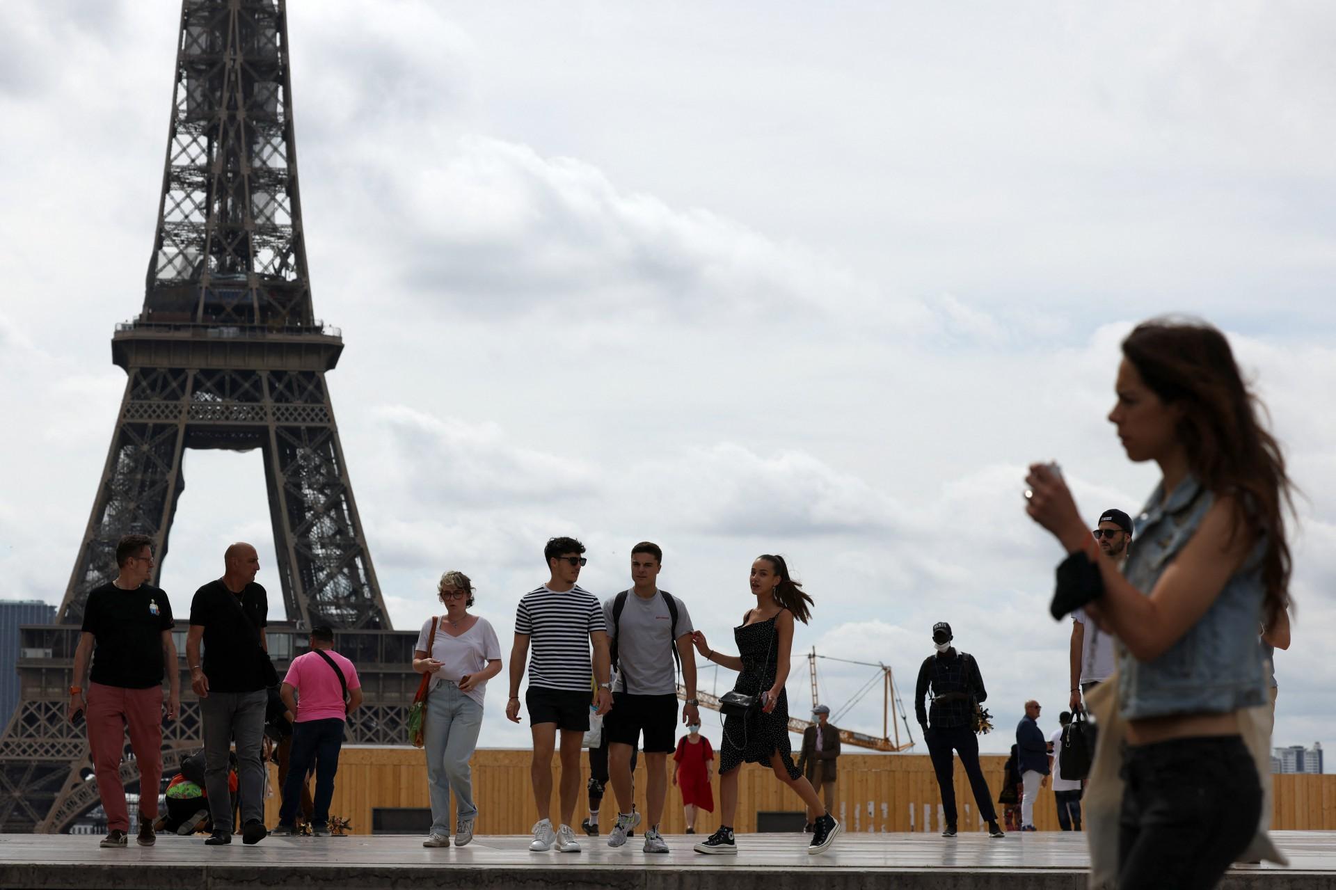 Pedestres caminham na praça do Trocadero visto que a Torre Eiffel é vista na segunda planta, em Paris, em 17 de junho de 2021, pois o fim da obrigatoriedade de uso de máscaras ao ar livre passa a vigorar a partir de 17 de junho e o levantamento do toque de recolher a partir de 20 de junho, graças a uma melhoria mais rápida do que o esperado na situação da saúde. (Foto de Thomas COEX / AFP)
