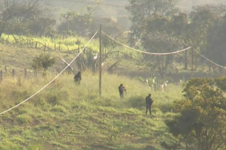 Policiais procuram o homem em mata local. (Foto: Reprodução/TV Anhanguera)