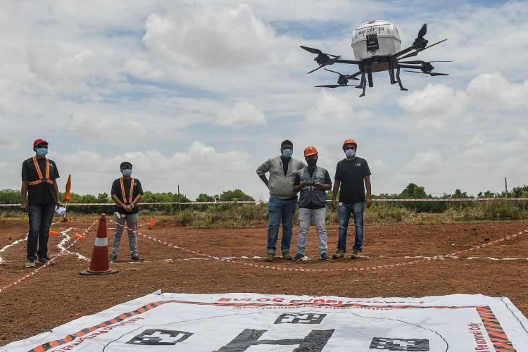 Os técnicos pilotam um drone pertencente à Throttle Aerospace Systems (TAS), que voa além da linha de visão visual (BVLOS) para entregar suprimentos médicos que salvam vidas, na Índia (Foto: Manjunath Kiran / AFP)