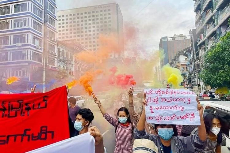 Esta foto tirada e recebida como cortesia de uma fonte anônima via Facebook em 26 de junho de 2021 mostra manifestantes marchando com faixas e sinalizadores enquanto participam de uma manifestação contra o golpe militar em Yangon, Mianmar (Foto: FACEBOOK / AFP)