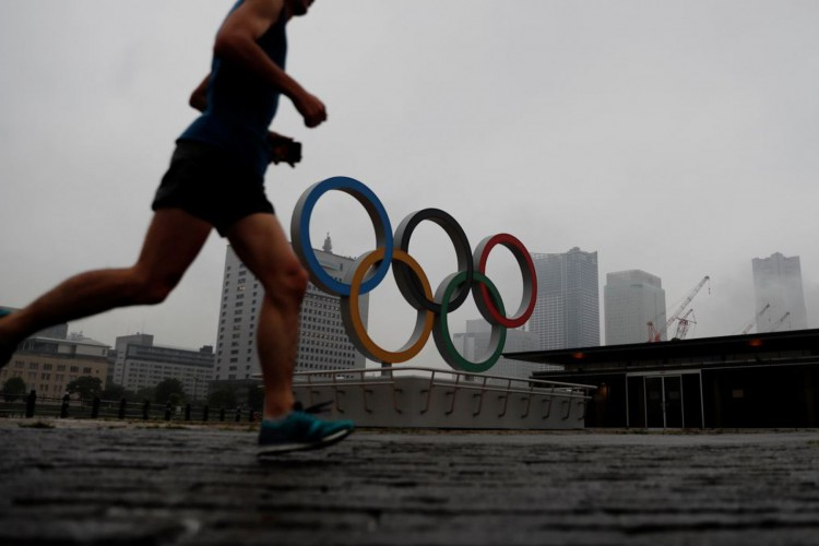A jogger runs past a newly installed Olympic rings for celebrating the 2020 Tokyo Olympic Games in Yokohama, Japan, June 30, 2021.   REUTERS/Kim Kyung-Hoon (Foto: REUTERS/Kim Kyung-Hoon)