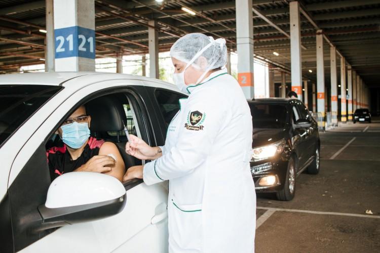 Vacinação em Fortaleza é feita por meio de agendamento. Nesta semana, já há agendamento para pessoa nascidas em 1989. Na foto, mulher recebe imunizante em drive-thru na Capital (Foto: Fernanda Barros)