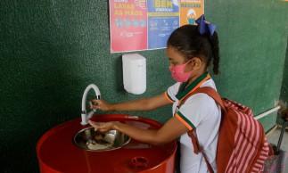 Os estudantes são submetidos a uma fila para higienização das mãos e aferição de temperatura