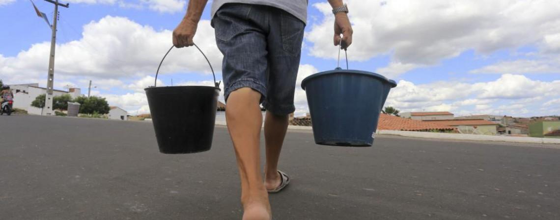 Homem carrega baldes com água (Foto: FABIO LIMA/O POVO)