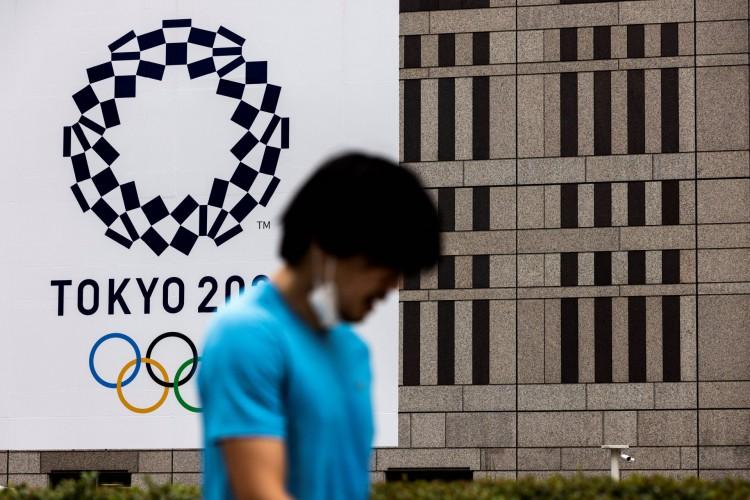 Um homem passa por um logotipo dos Jogos Olímpicos de Tóquio 2020 em Tóquio em 15 de julho de 2021 (Foto: Behrouz MEHRI / AFP)