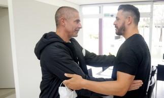 Meia Giuliano cumprimenta técnico Sylvinho no CT do Corinthians