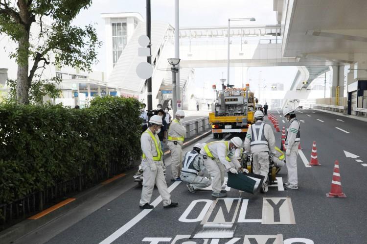 Trabalhadores pintam marcações rodoviárias para uma pista prioritária em Tóquio em 18 de julho de 2021, que será usada para transportar pessoas durante os Jogos Olímpicos de Tóquio 2020(Foto: STR / JIJI PRESS / AFP)