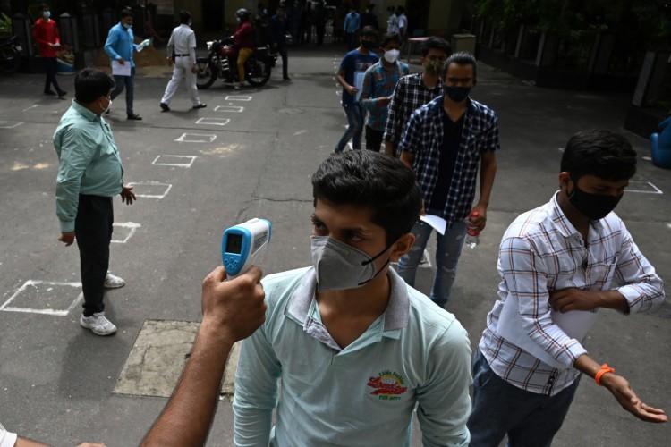 Os alunos fazem fila para entrar em uma sala de exames para fazer o teste do Exame de Admissão Conjunta (JEE) estadual em meio à pandemia de coronavírus Covid-19 em Calcutá em 17 de julho de 2021 (Foto: DIBYANGSHU SARKAR / AFP)